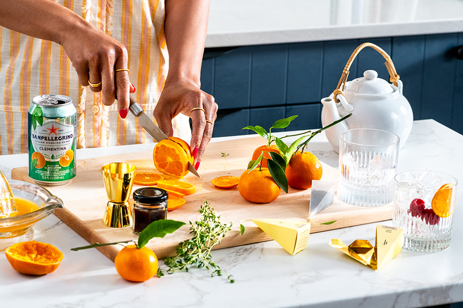 A woman cuts fresh clementines while preparing the recipe. Photographed by Laura Chase de Formigny.