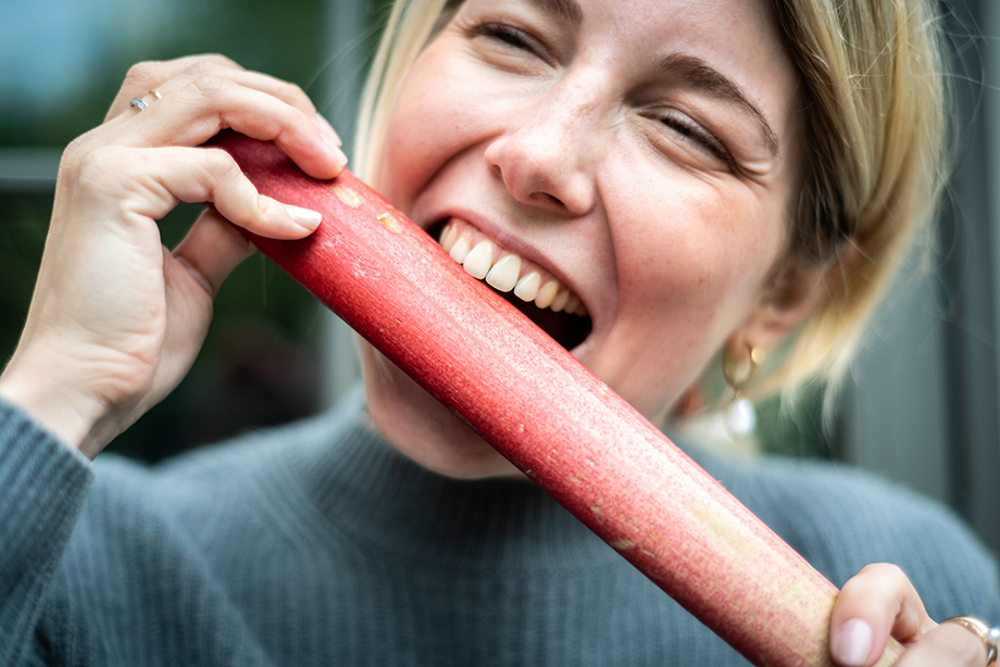 A playful shot of a woman pretending to eat a rhubarb stalk. Photography by Lola Akinmade.