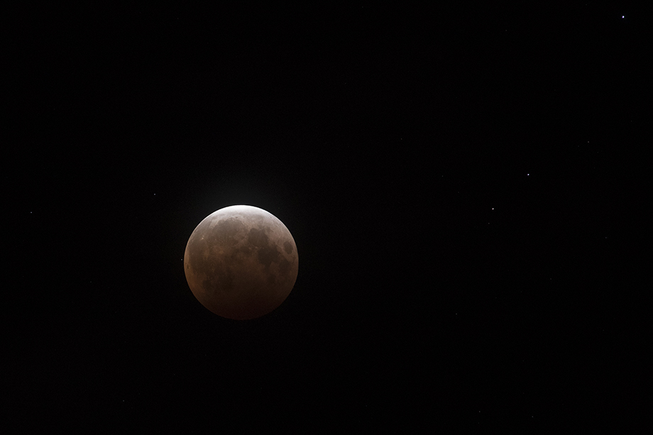 A supermoon, the biggest and brightest full moon of the year, coincides with a total lunar eclipse making the Moon appear red over the skies of Honolulu, Hawaii, U.S. May 26, 2021. Photography by Marco Garcia for Reuters.