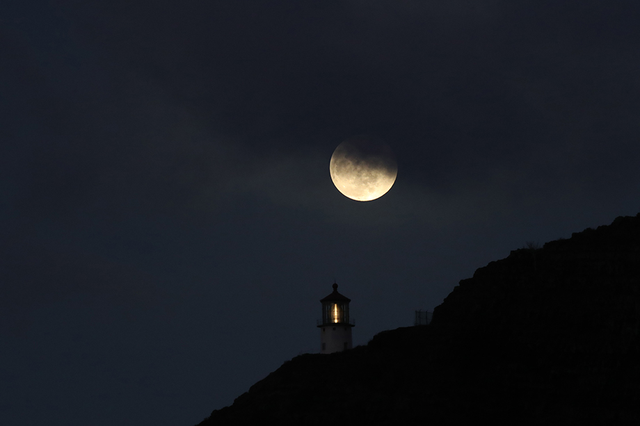 Supermoon photographed next to Makapu'u Lighthouse in Honolulu, Hawaii. Photography by Marco Garcia for Reuters.