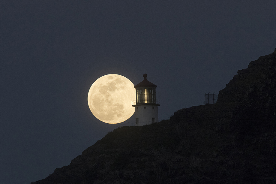 Supermoon perfectly positioned next to Makapu'u Lighthouse in Honolulu, Hawaii. Photography by Marco Garcia for Reuters.