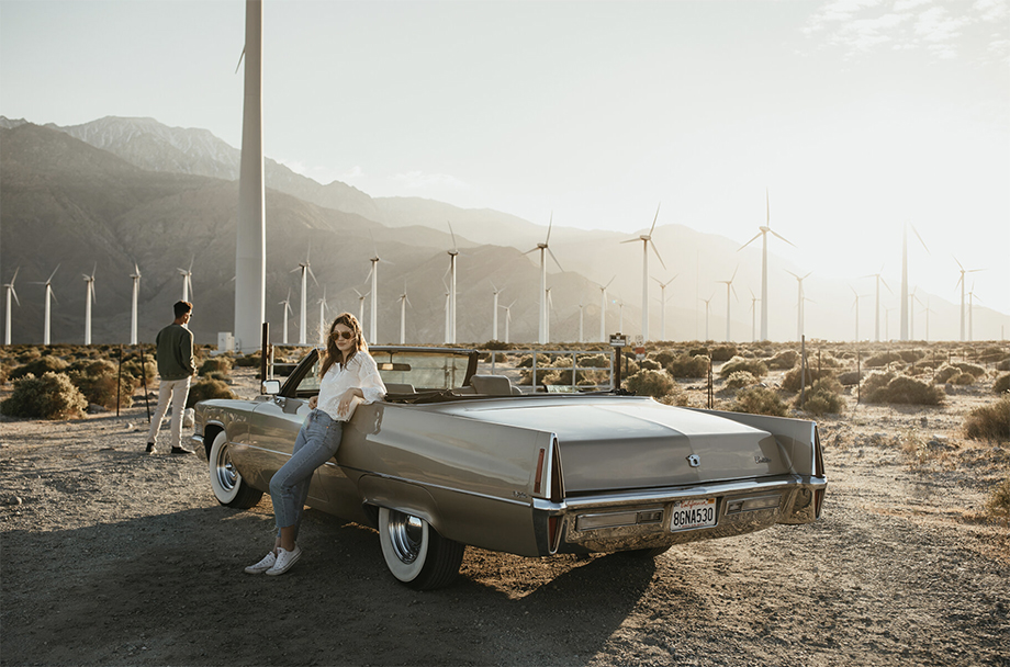 Models pose with a Cadillac convertible against windmills in the background. Photographed by Marissa Roseillier for American Optical.