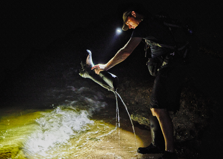 """Fossil hunter pouring water out of his shoe at night for Matthew Rakola's """"My Former Future Self"""""""