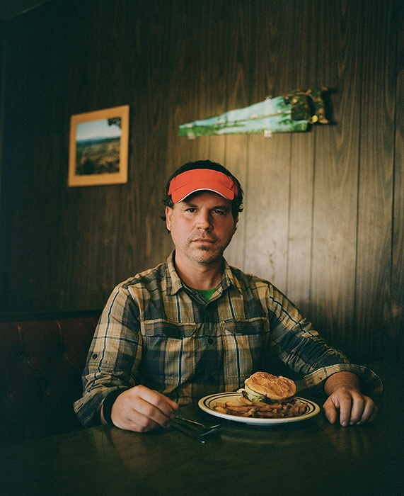 Rue McKenrick stares directly at the camera while sitting at a diner in Bend, Oregon. Photographed by Michael Hanson for Backpacker Magazine.