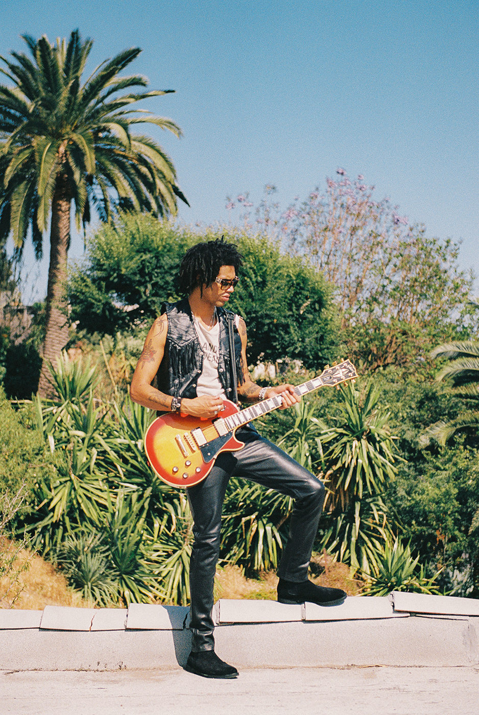 Model standing with electric guitar on roof shot on film by Michael Julius for New Republic Footwear Sonoma campaign