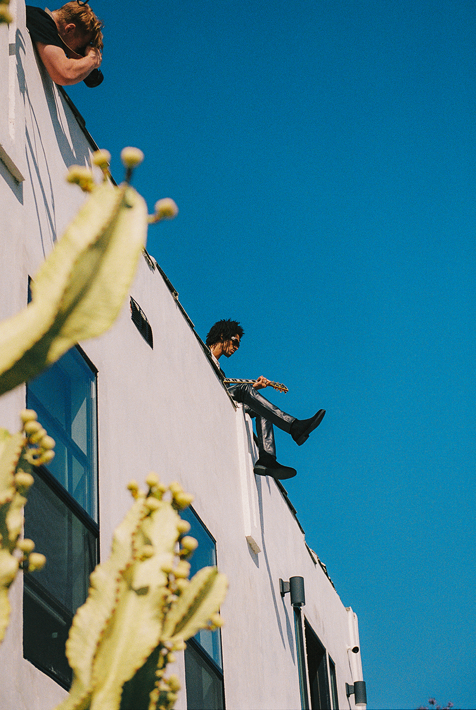 Model Jaxon Rose playing guitar on roof shot from below by Michael Julius for New Republic