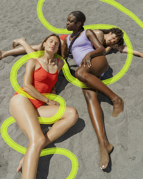 Three models lay in the sand with painted designs shot by Molly Strohl for Shop Sounds