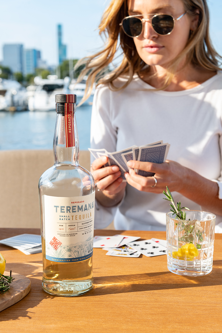 Woman playing cards on a boat with a near empty glass of Teramana Tequila garnished with citrus and rosemary shot by Morgan Ione