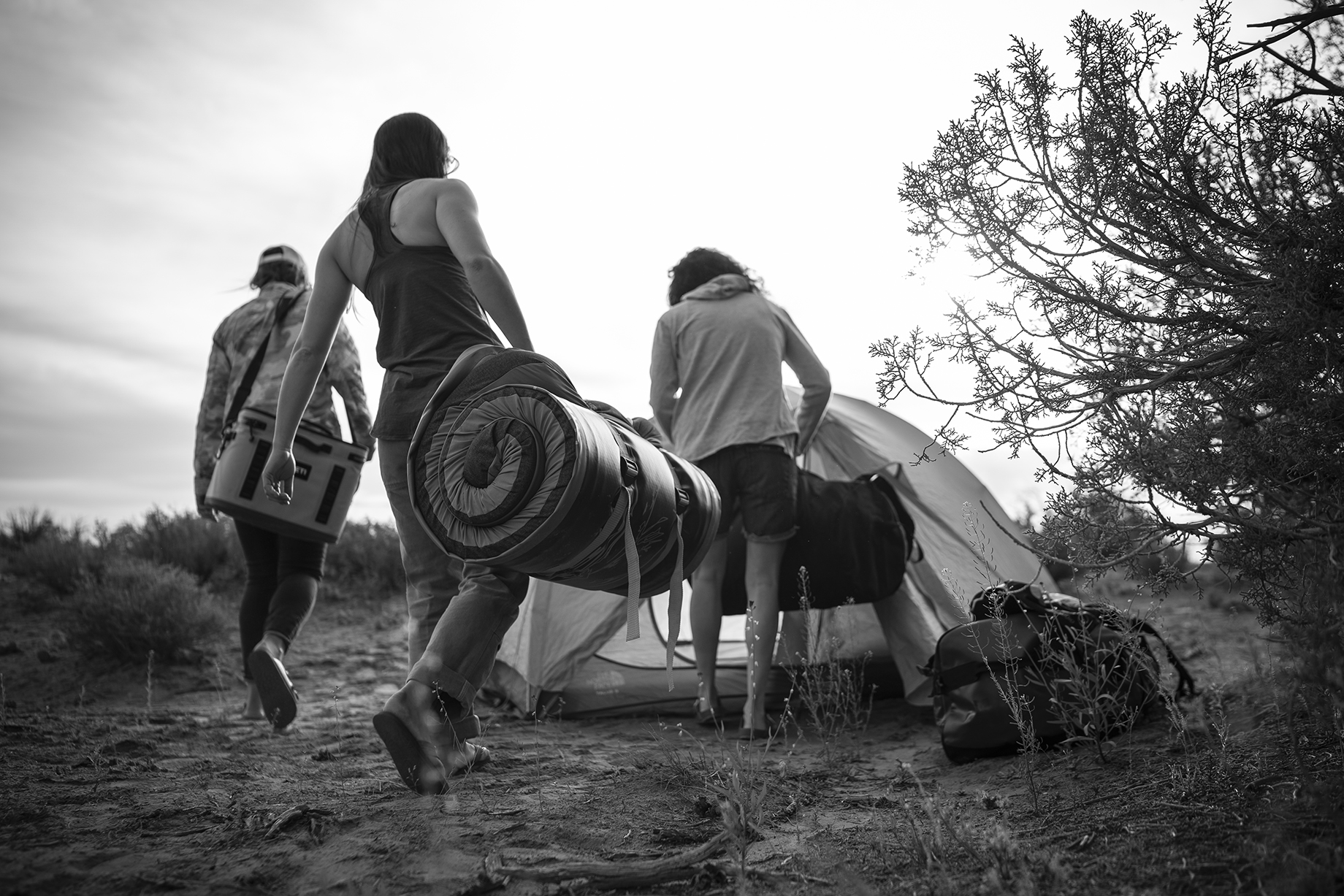 Black and white image of three woman setting up tent with rolled up Hest mattress in Moab desert shot by Motofish