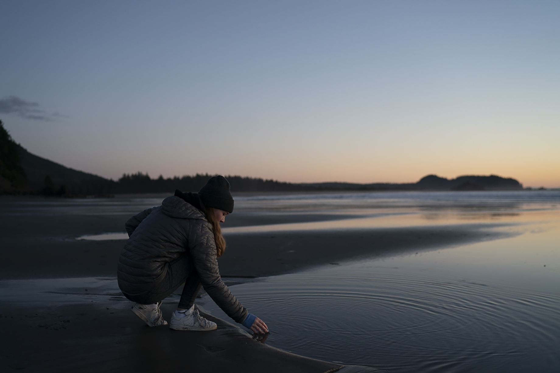 Young woman touching still waters on a cold Washington beach at sunset shot by Motofish for Hest.