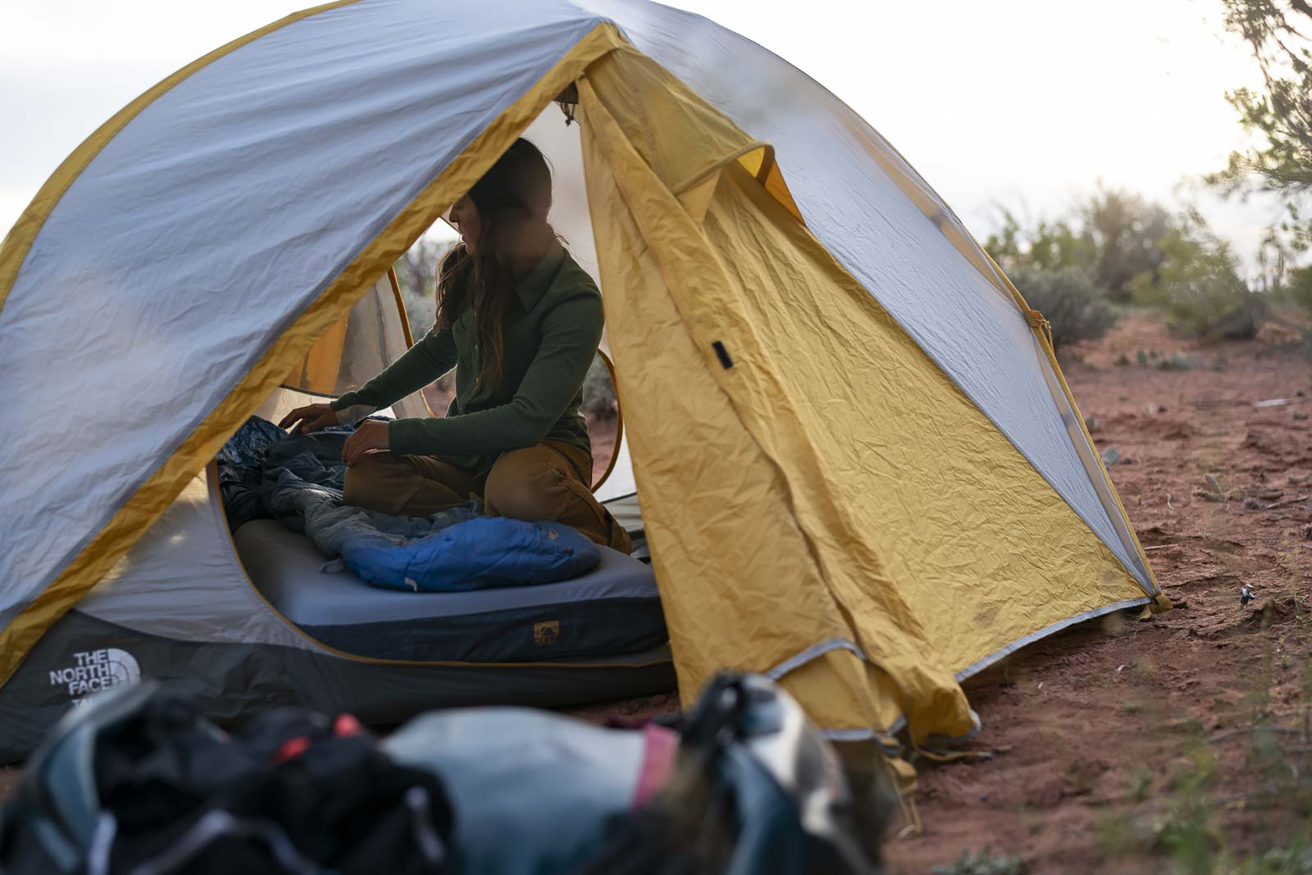 Woman sets up sleeping bag on top of Hest mattress in Moab desert shot by Motofish