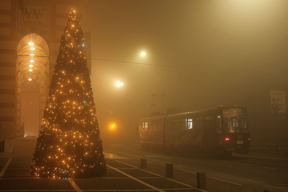 A tram waits to depart at a stop across from Sarajevo's City Hall on a heavily polluted night.Photography by Nick St. Oegger.