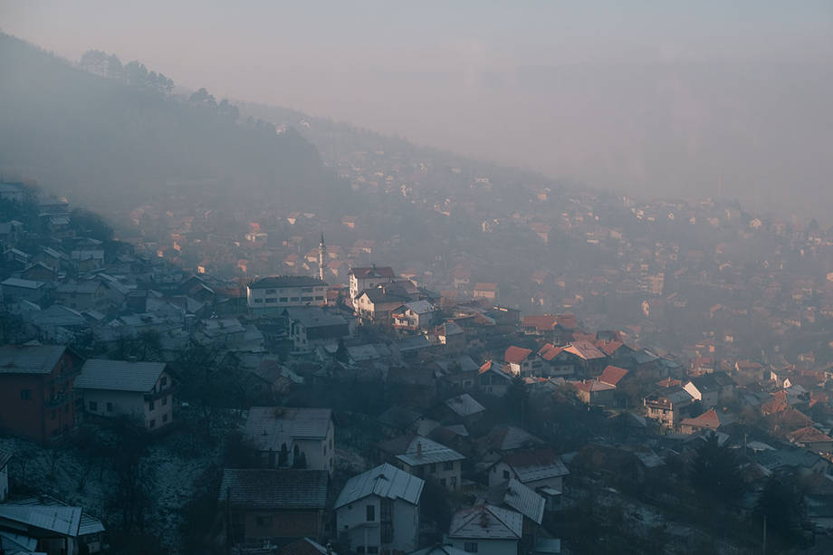 A neighborhood in the hills above Sarajevo on a heavily polluted day. Individual households stretch into the hills on either side of the city, where many lower income families live and rely on poor quality fuels burned in stoves or fireplaces for heating. Photography by Nick St. Oegger.
