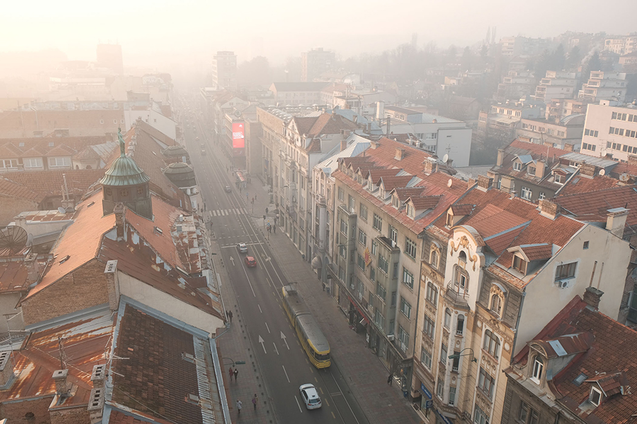 Smog hangs in the distance of Sarajevo in this view down Maršala Tita street in the city center. Photography by Nick St. Oegger.