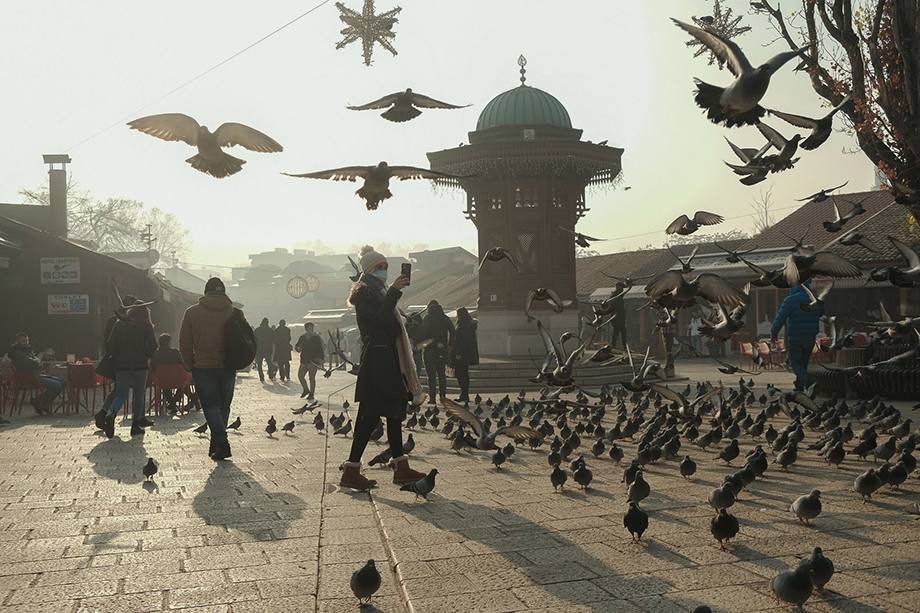 """A woman takes photos in Sarajevo's iconic """"Pigeon Square"""" on a day when the city was one of the most polluted in the world, with an Air Quality Index (AQI) rating of 350. During the winter, Sarajevo often reaches the position of world's most polluted city, outranking usual placeholders like New Delhi, Kolkata, Beijing and Dhaka.Photography by Nick St. Oegger."""