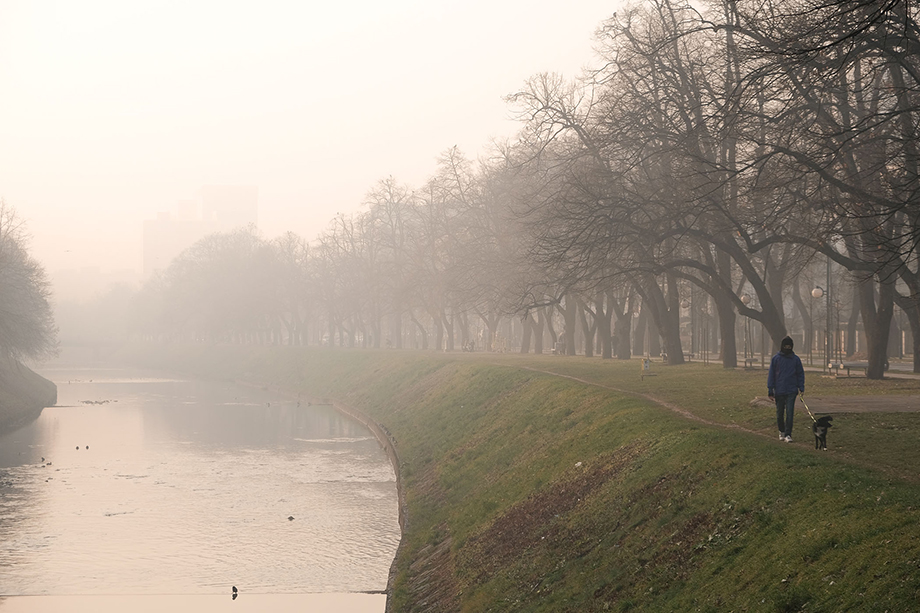 A man walks his dog along the banks of the Miljacka river on a heavily polluted evening in Sarajevo. Photography by Nick St. Oegger.