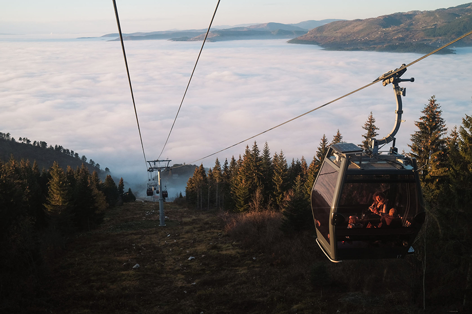 People ride a cable car up Mt. Trebević as Sarajevo is obscured by a layer of fog and pollution. Temperature inversion, which occurs when air at high altitudes becomes warmer than the air below, often keeps smog trapped in the city below. Photography by Nick St. Oegger.