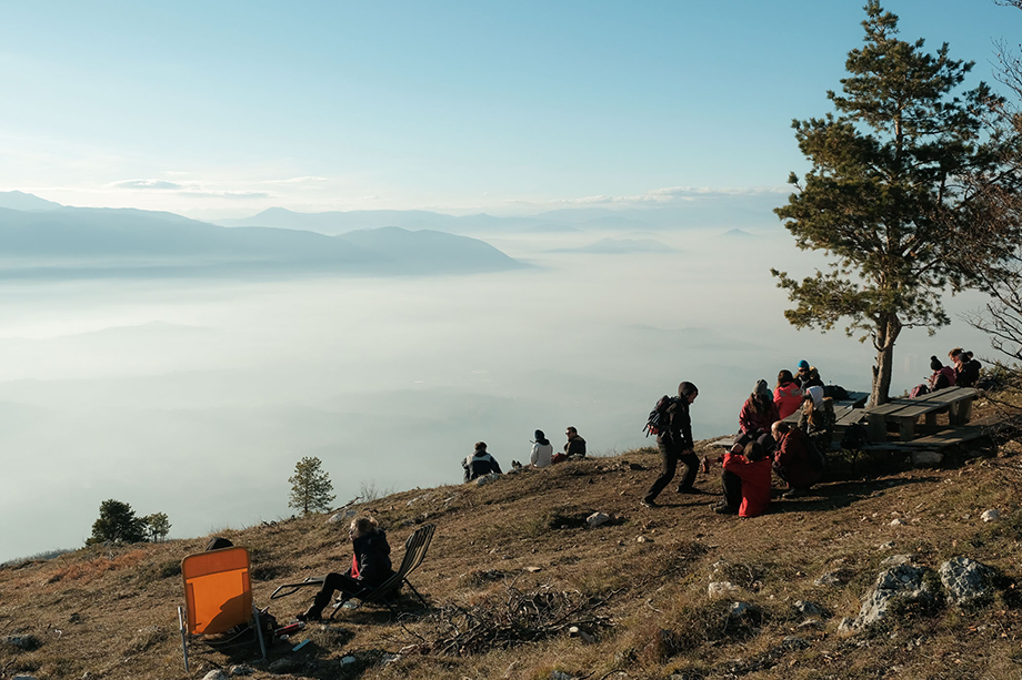 People picnic and take in the views near a mountain hut on Mt. Trebević as a layer of smog blankets Sarajevo below. The mountain often becomes incredibly crowded on weekends, with visitors spending time in the sun and fresh air of the mountain.Photography by Nick St. Oegger.
