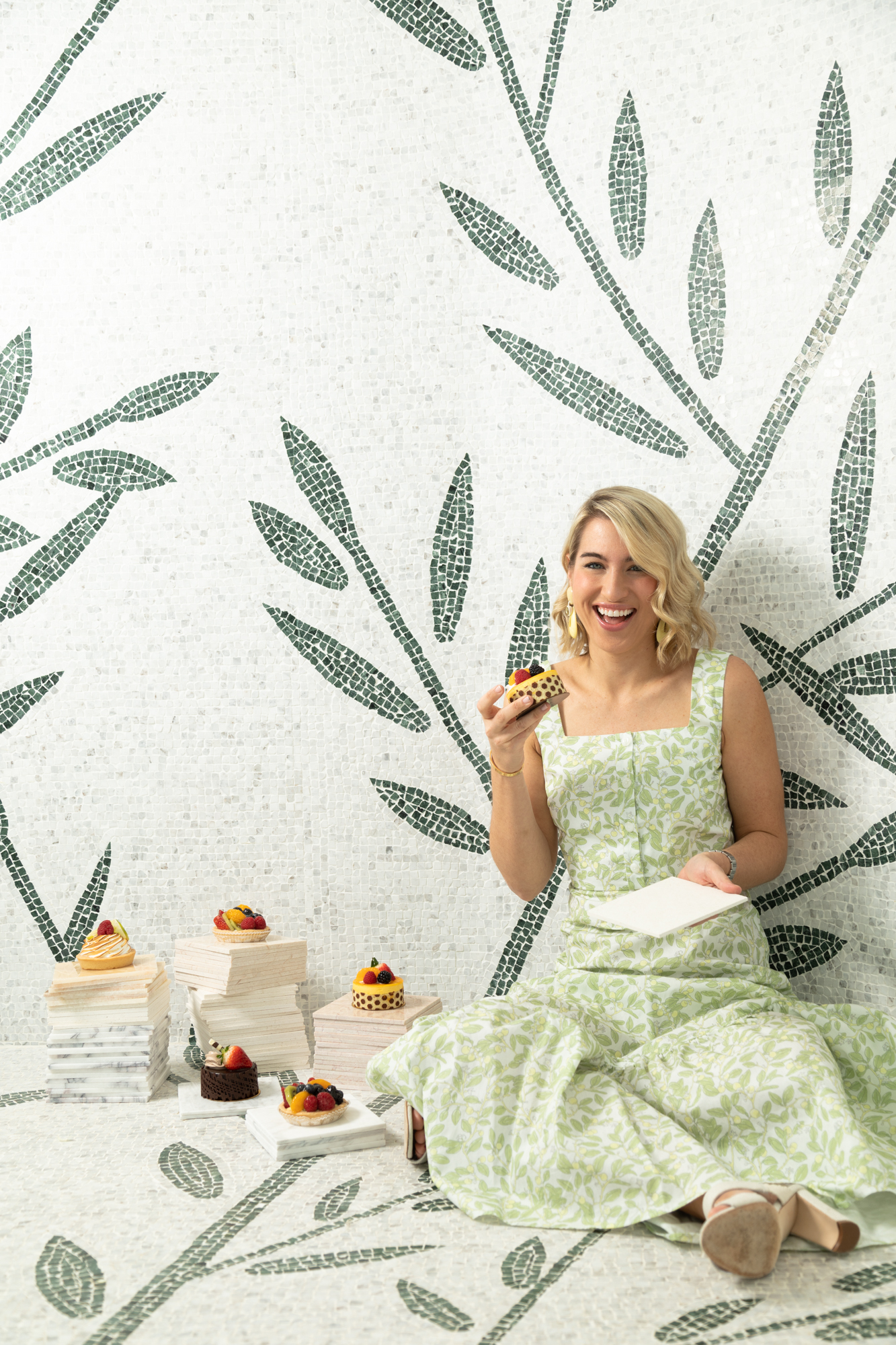 Patrick Heagney photographs a laughing Clary Bosbyshell as she sits in a marble tiled shower eating picturesque pastries