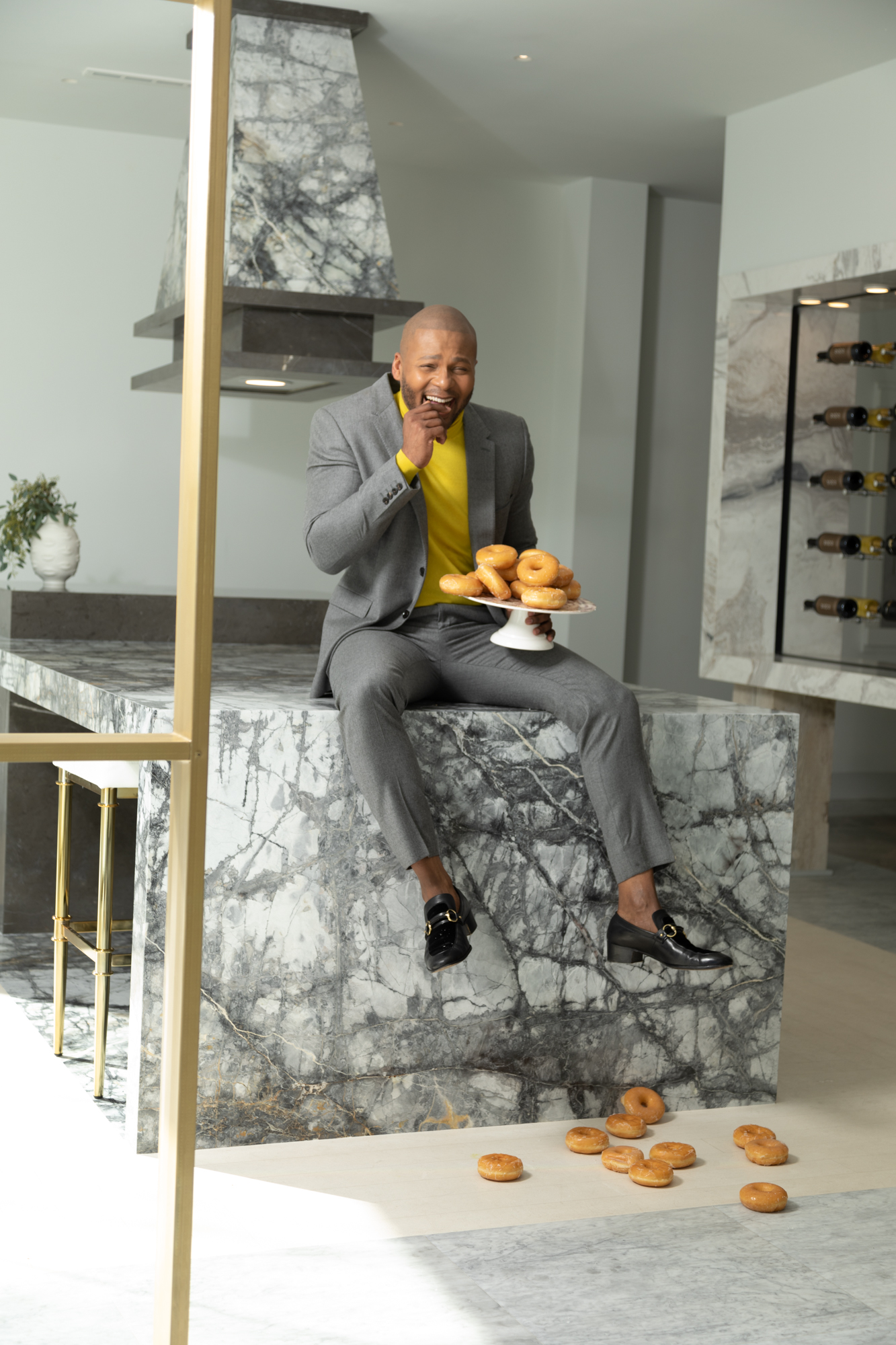 Patrick Heagney photographs laughing designer Michel Smith Boyd as he drops his donuts for Temmer Marble