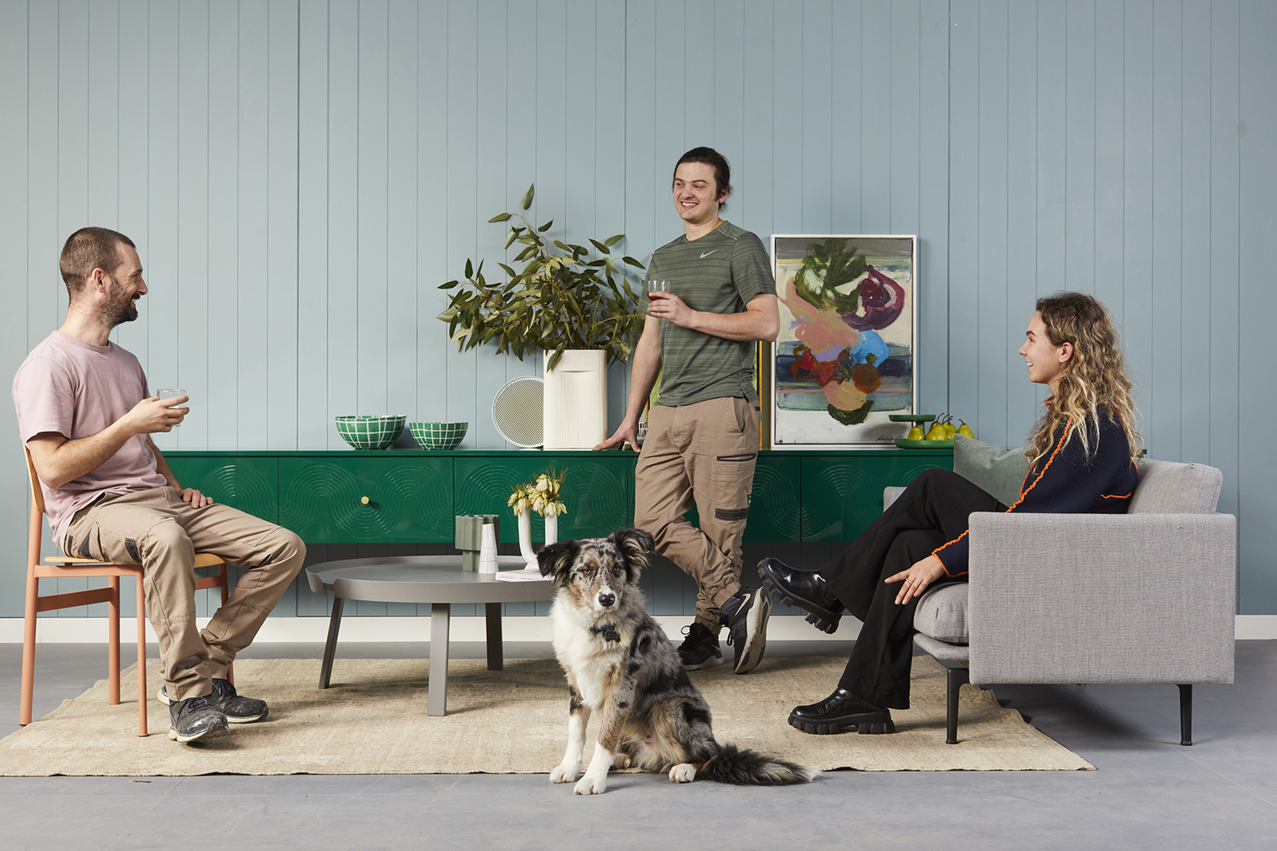 The Ensemble design team posing as subjects with an Australian Shepard in front shot by Peter Tarasiuk