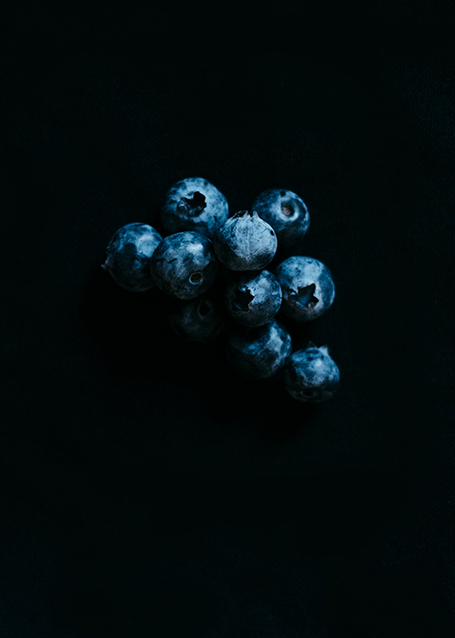 Blueberries photographed against a black background, food photographer los angeles, hire food photographer los angeles, food photography los angeles, dark light food photography, chiarocsuro food photography, chiarocsuro, dark lighting, fruits photography, vegetables photography