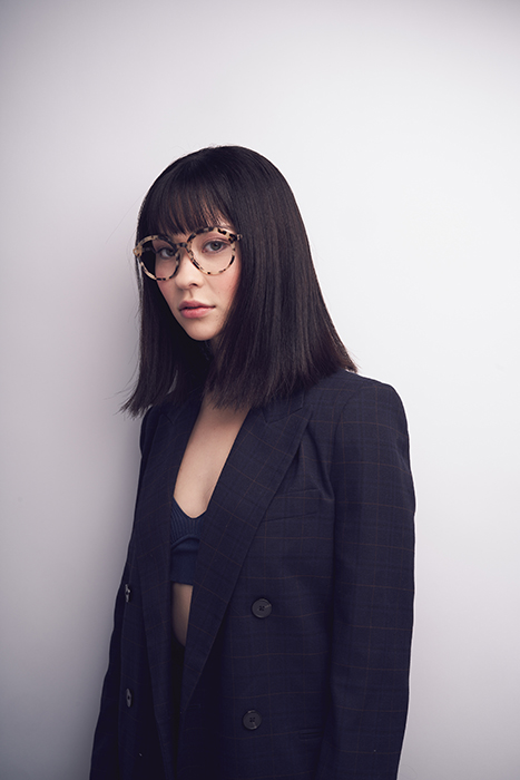 A female model looks at the camera while wearing oversized glasses by Richard Schmon