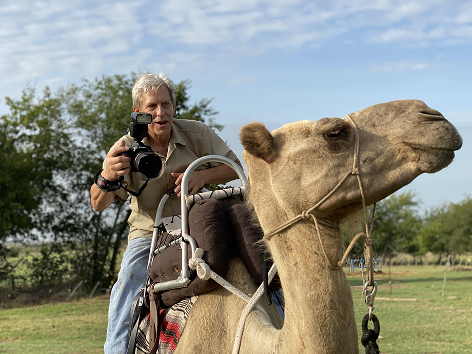 Scott Van Osdol riding a camel while taking photos.