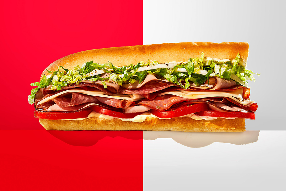 A Jimmy John's sub photographed against a red and white backdrop. Photography by Teri Studios, Teri Campbell, food photography, food photographer, commercial food photographer, commercial food photography, commercial food styling, commercial food stylist, sandwich shop, Jimmy John's, fastfood, sandwich chain, sandwich, sandwiches, food branding, phoode
