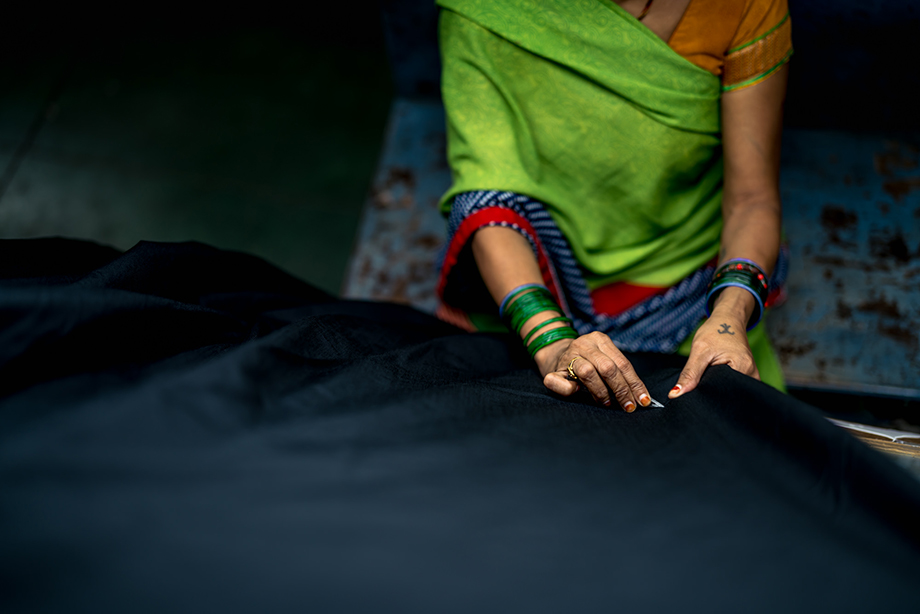 A worker sews a garment at a factory. Photography by Tim Gerard Barker.