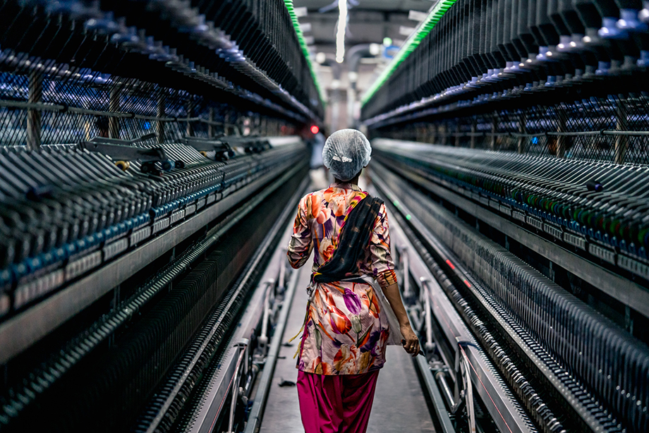 A factory worker in India walks through a line of textile machines. Photography by Tim Gerard Barker.