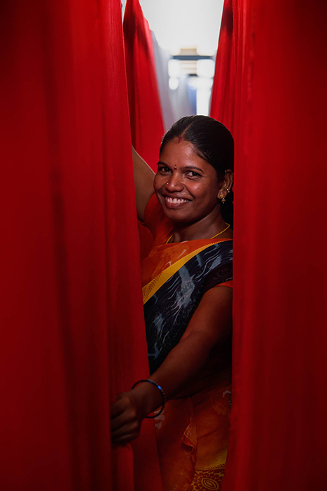 A female Zilingo employee in a factory in India smiles for the camera. Photography by Tim Gerard Barker.