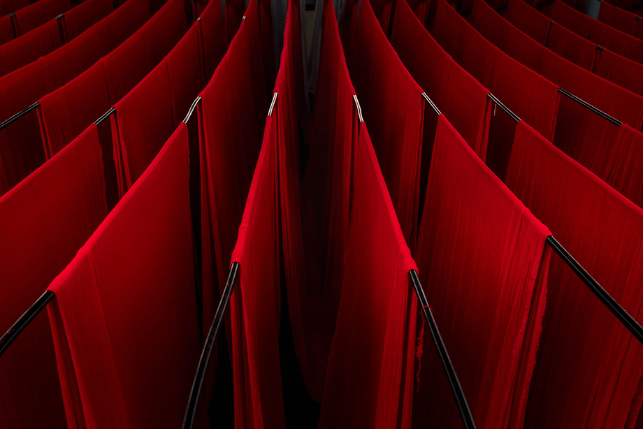 A sea of dyed red fabric hangs to dry in a factory in India. Photography by Tim Gerard Barker.