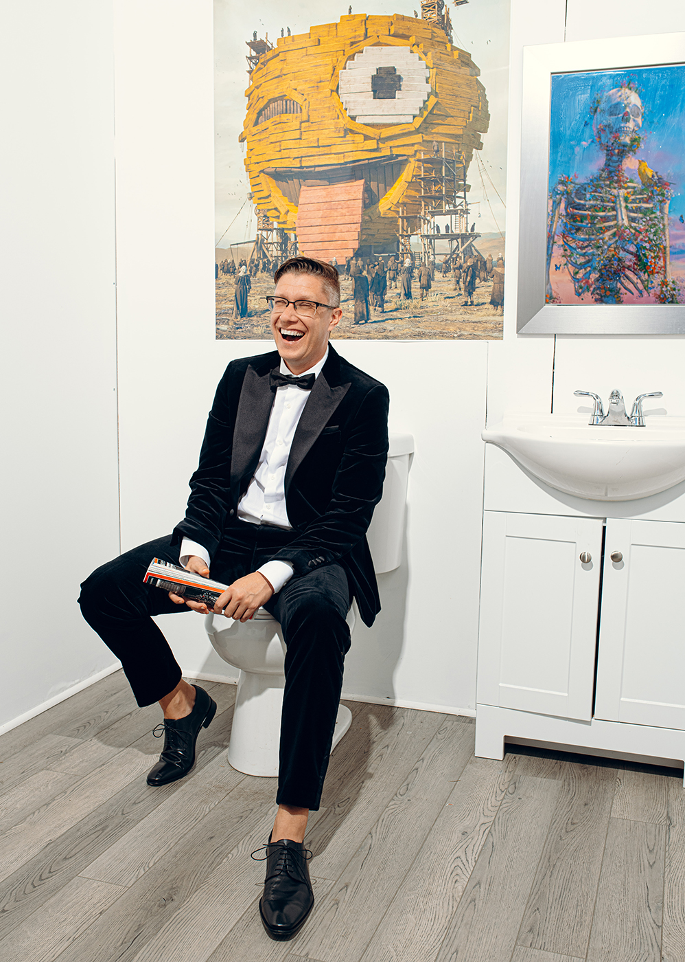 Beeple sitting on the toilet in his bathroom with his art on display behind shot by Will Crooks for British GQ