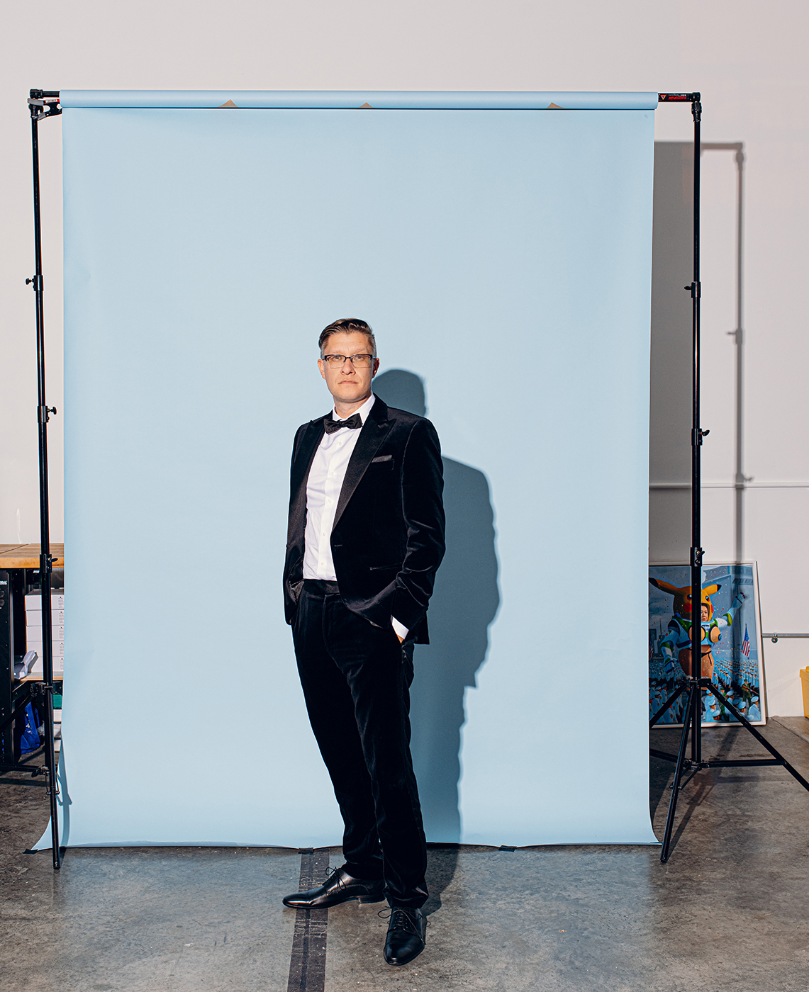 Beeple standing with his hands in his pockets in front of a light blue backdrop while wearing a tuxedo shot by Will Crooks for British GQ
