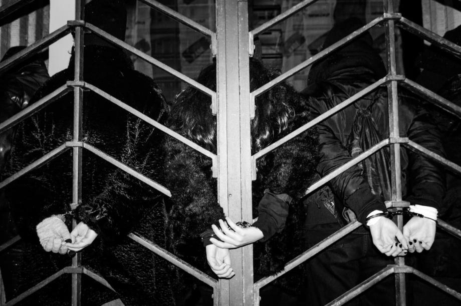 Three people handcuffed to a gate at Warsaw protests shot by Wojciech Grzedzinski for Republik Magazine