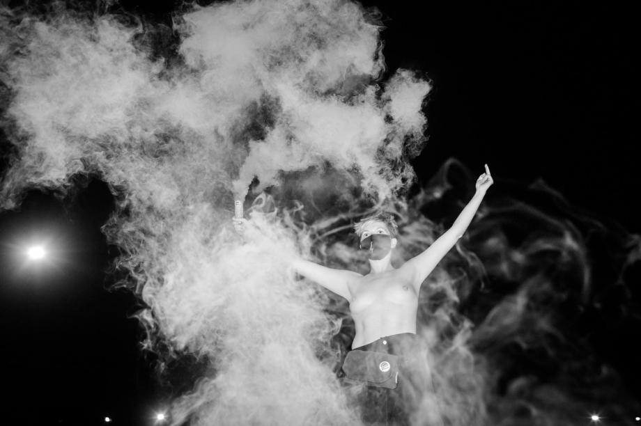 Woman amid smoke at Warsaw protests shot by Wojciech Grzedzinski for Republik Magazine