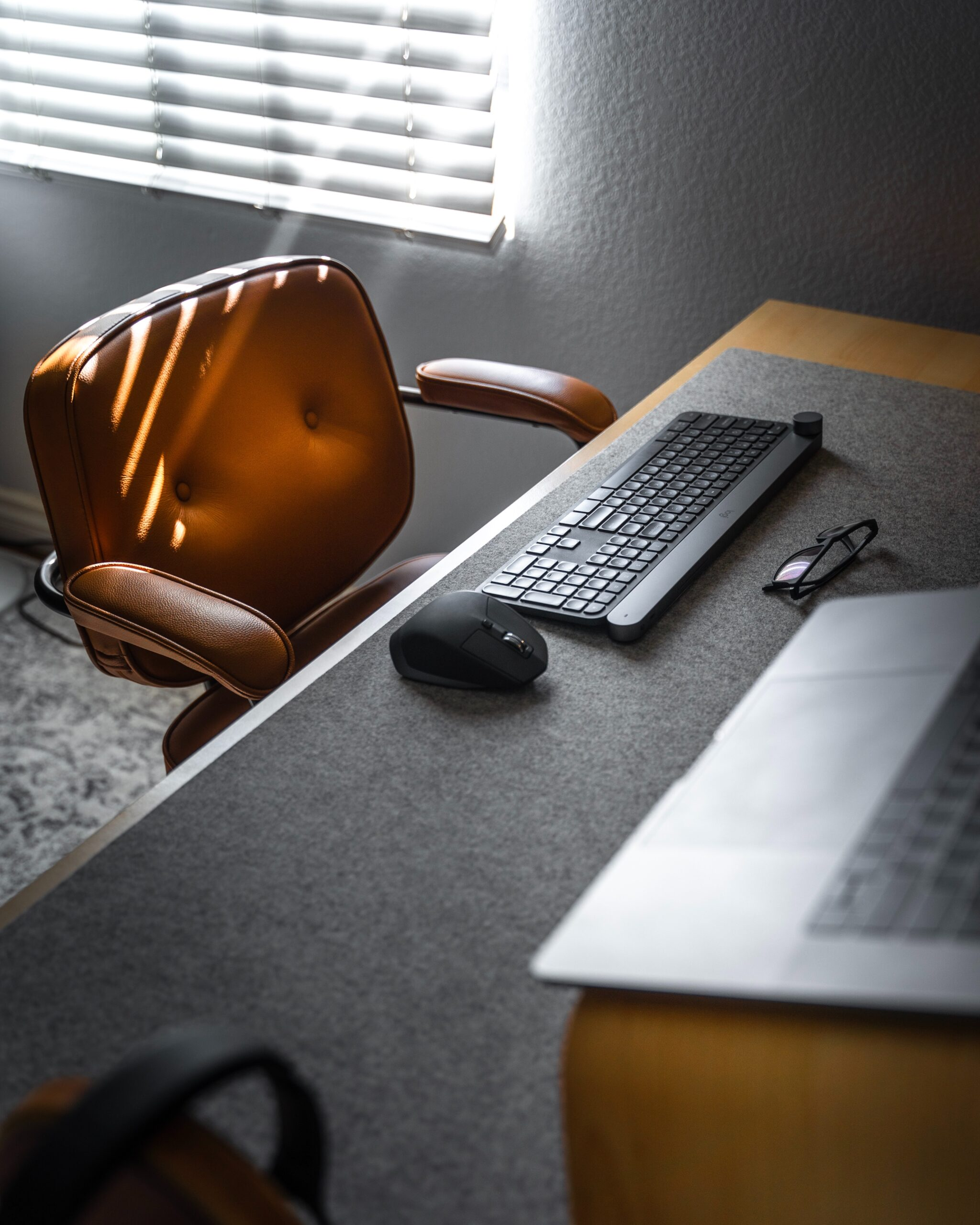 Photo of a lonely desk chair, keyboard, and computer by Michael Soledad on Unsplash