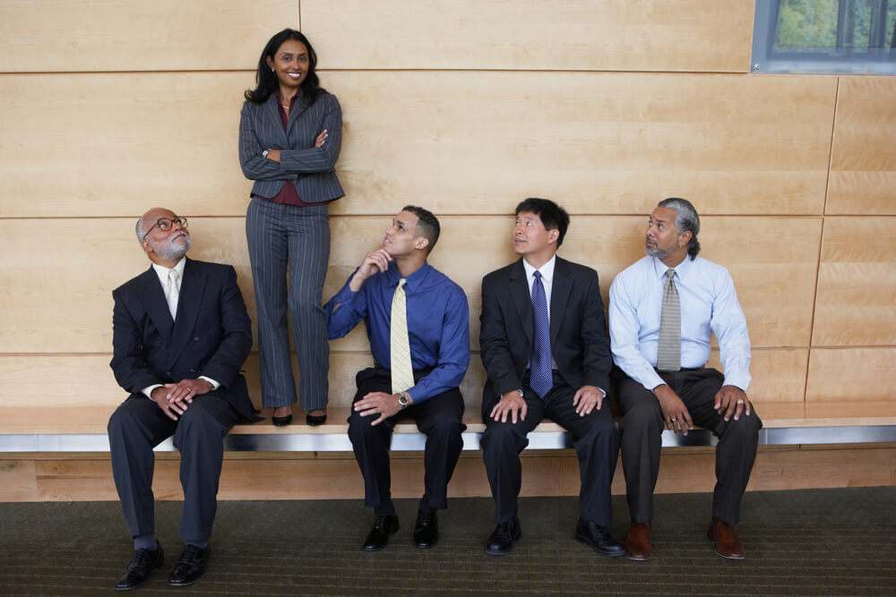 Woman Stands on Bench while Others Sit and Look Up to Her