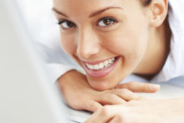 Closeup portrait of cute young woman with a laptop