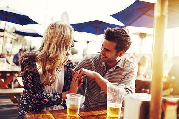 romantic couple drinking beer with artistic lens flare