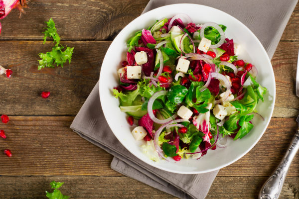 Fresh green salad with feta cheese and pomegranate. Top view