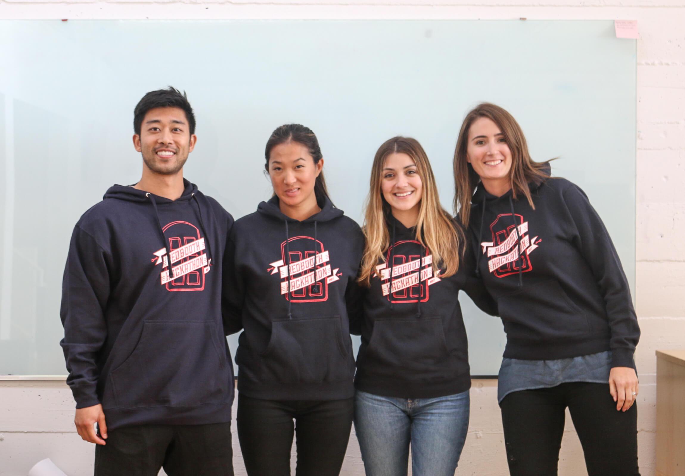 Redbooth hackathon participants pose with hoodies