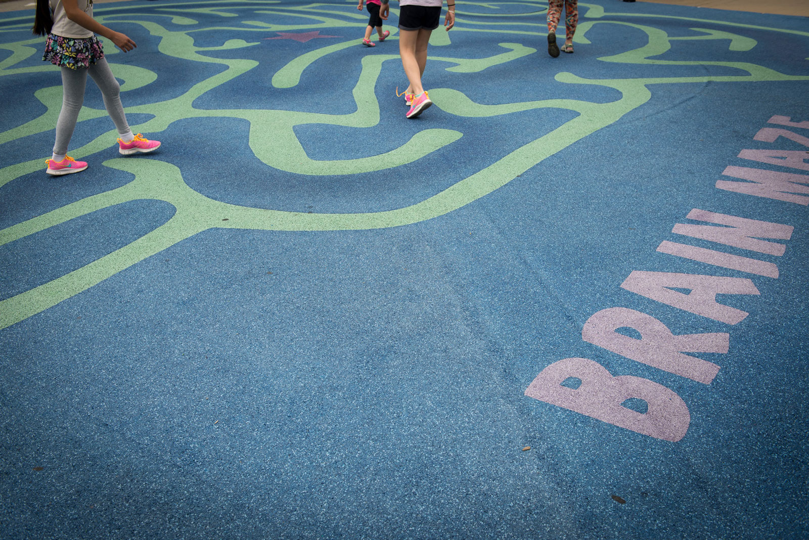 feet running through maze painted on concrete