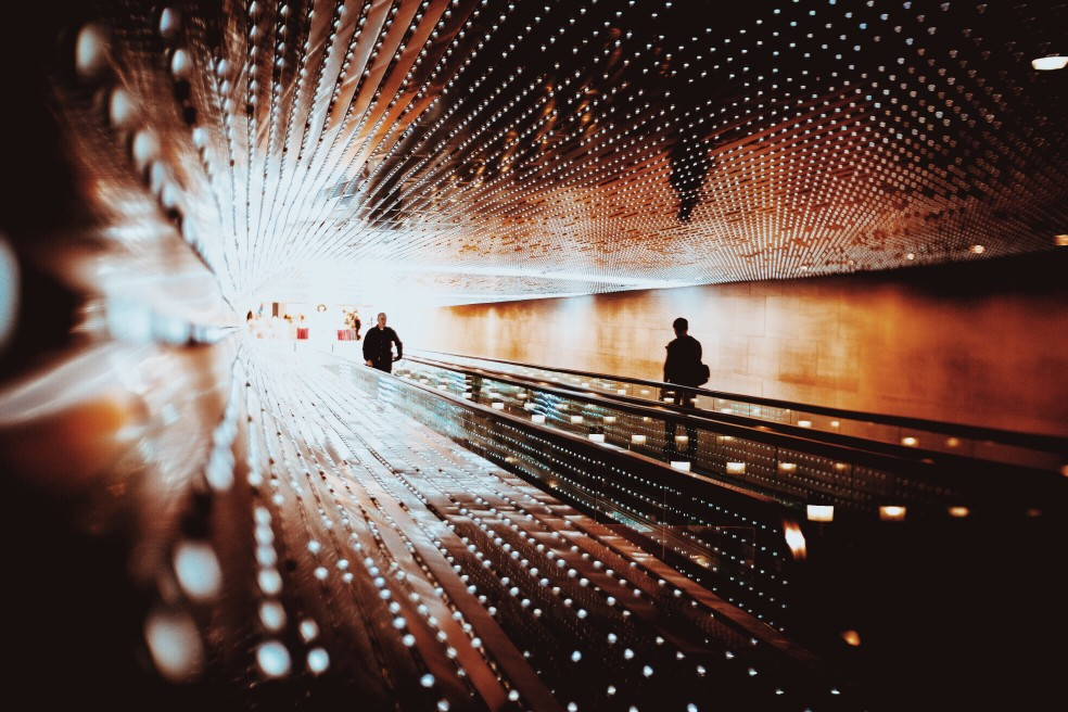 people walking through tunnel with light at the end
