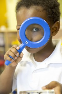 little boy uses magnifying glass