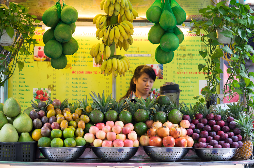 Vietnamese girl serving fresh tropical fruit juice_334104605