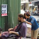 barber cut hair on street_269543330