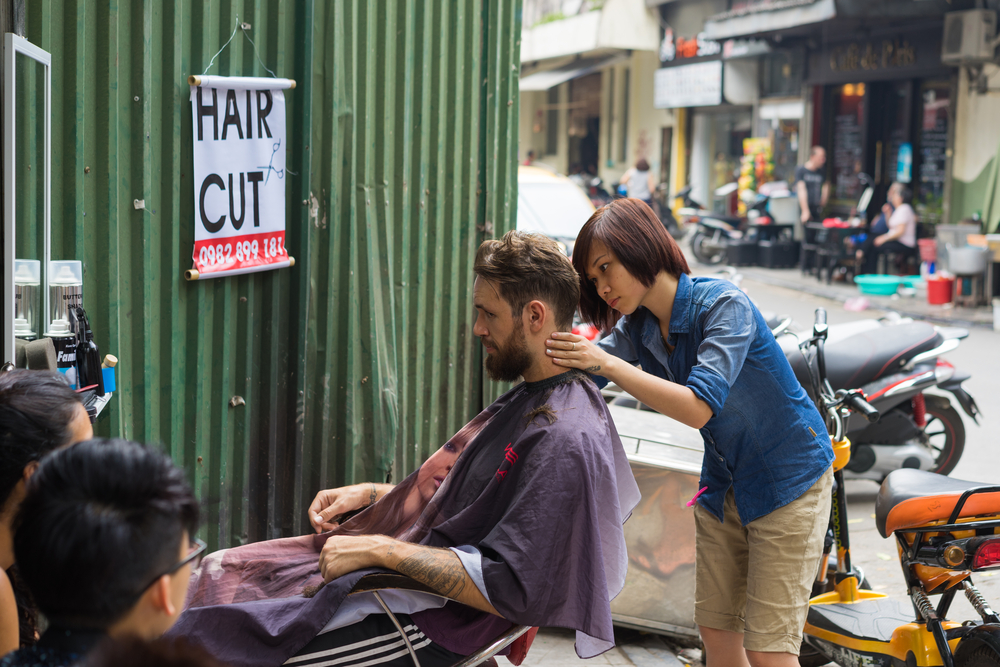 barber cut hair on street_269543330