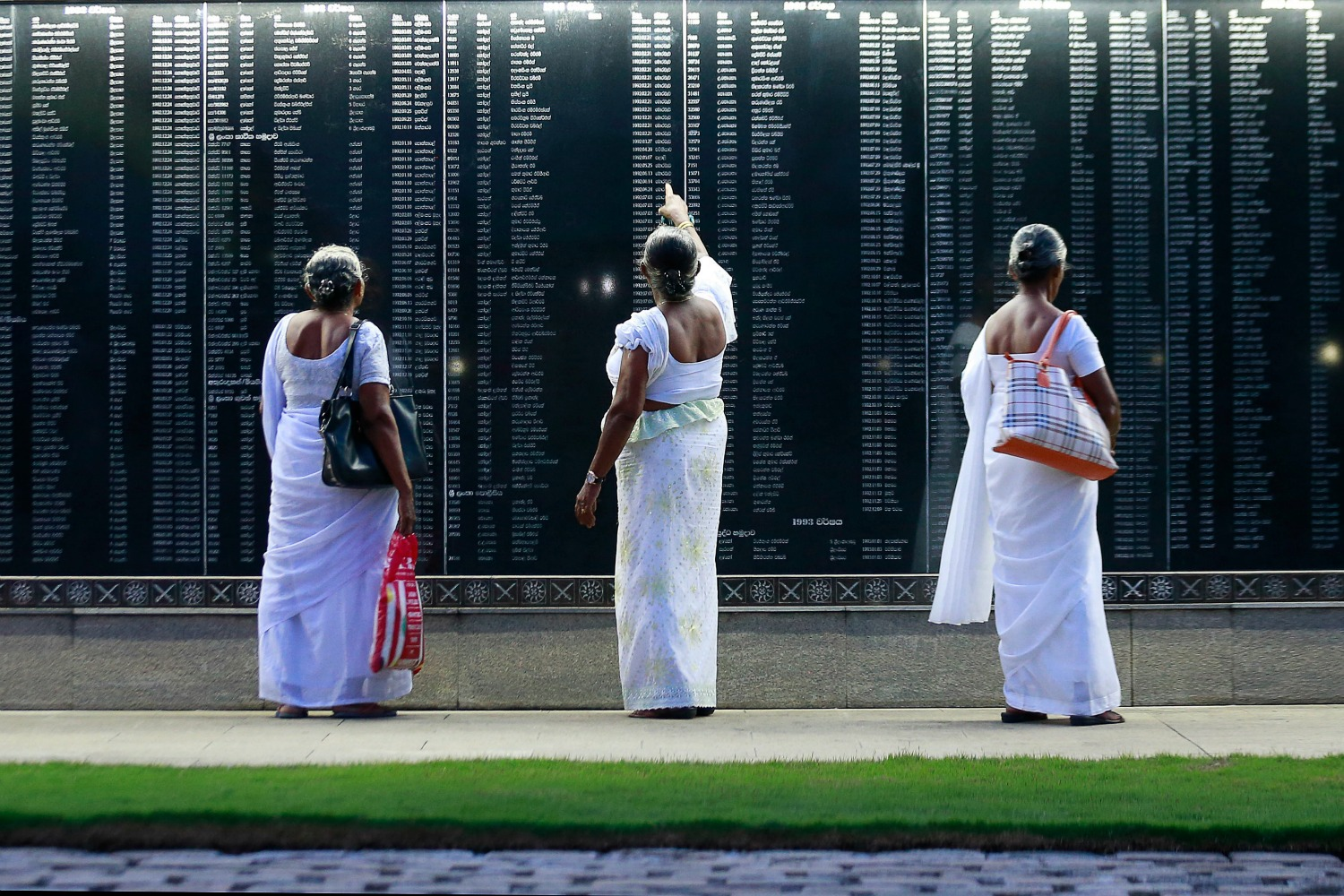 Sri Lankan mothers check for the names of their sons on a memorial to fallen soldiers.